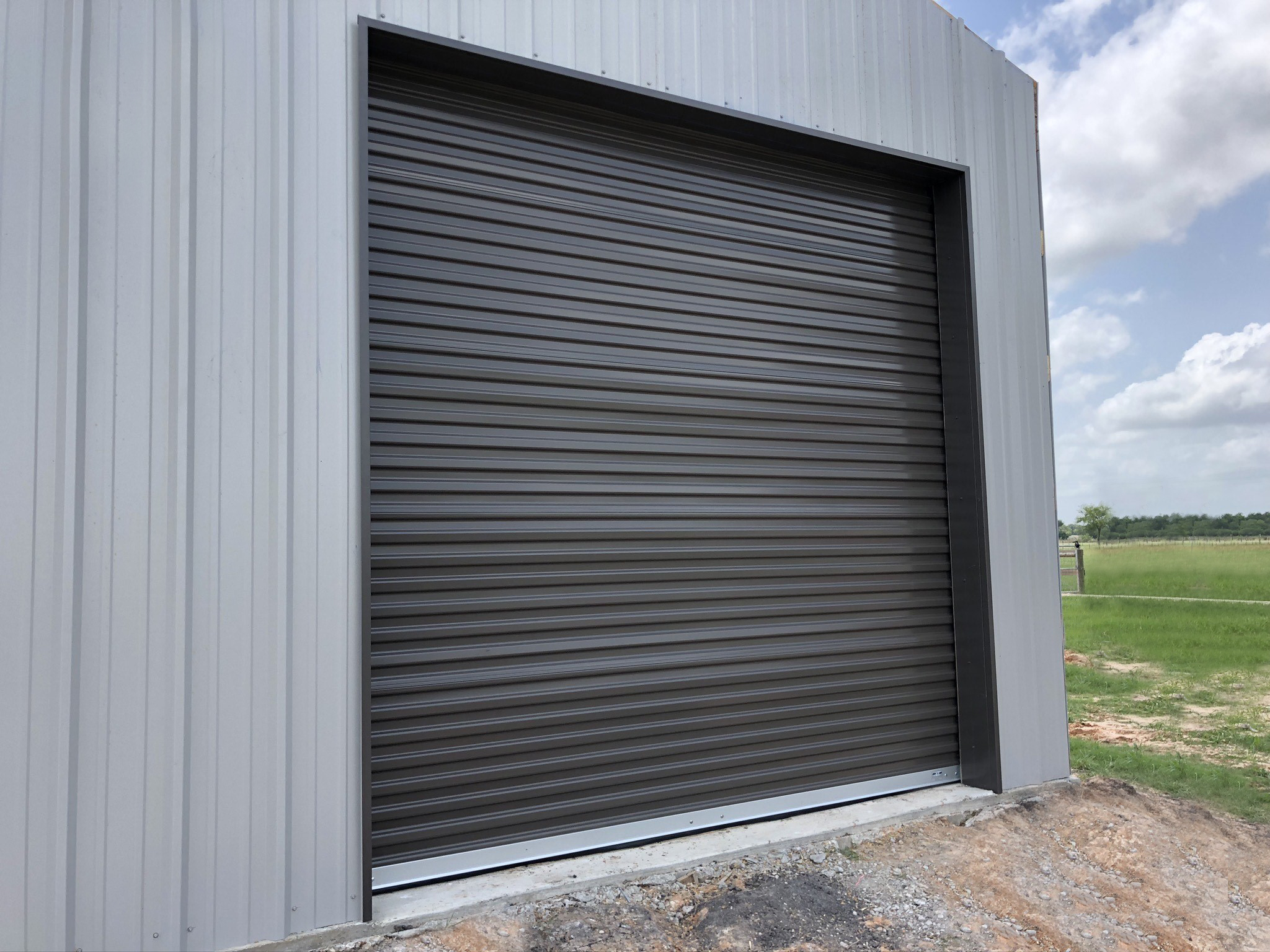 Select builders, Houston TX, Installed Gray Roll-Up Door on Shed