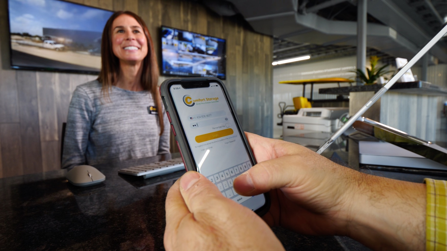 woman smiling and showing customer how to use the app to access his self-storage unit