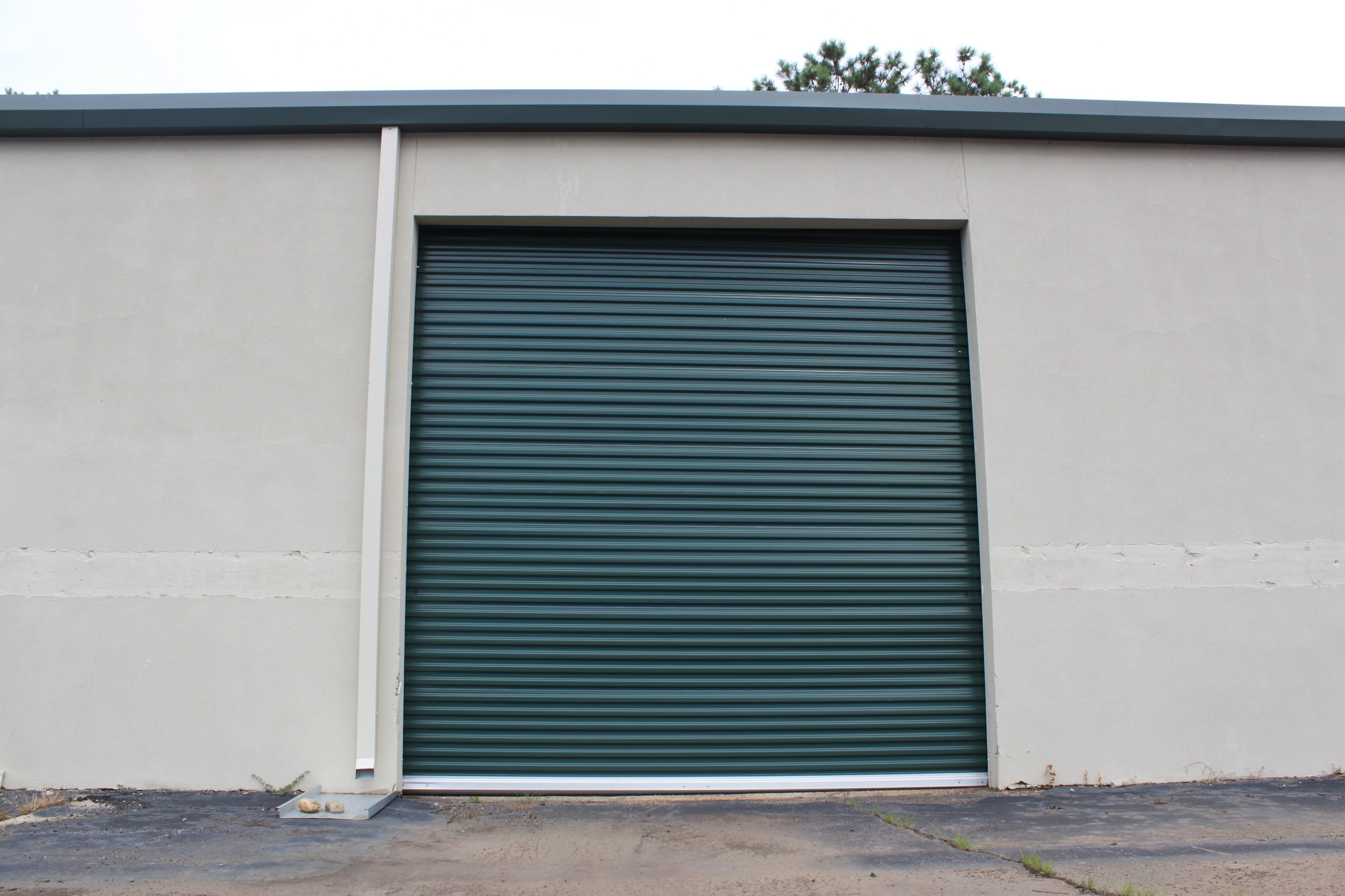 Green commercial roll up door at a facility