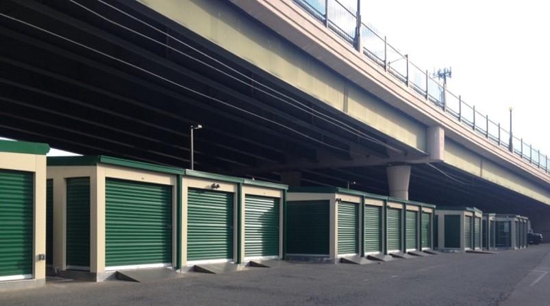 Green portable storage units under freeway