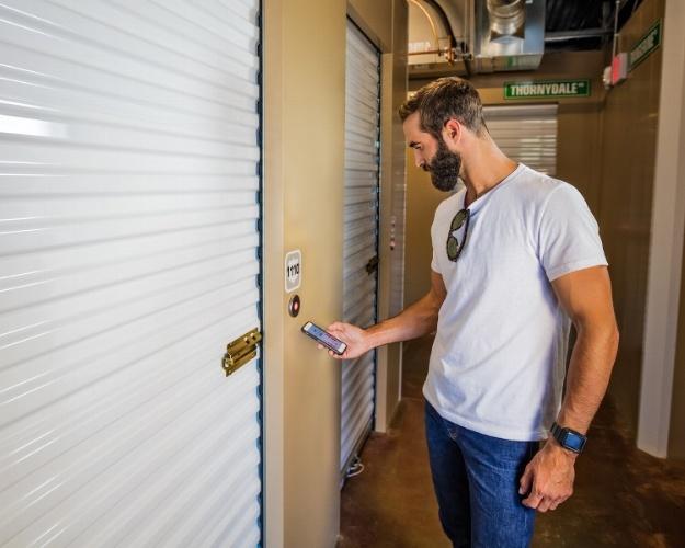 Man using Noke Smart Entry system to open self storage unit door
