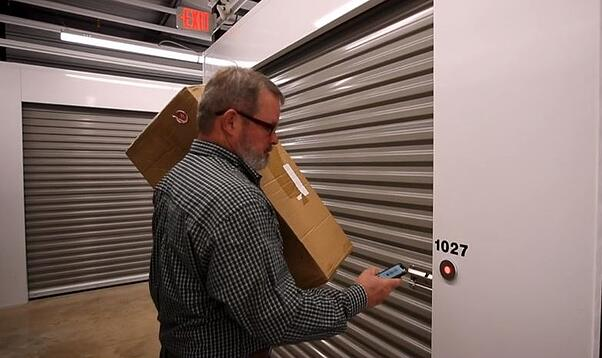 Man using smartphone to open the bluetooth lock on storage unit