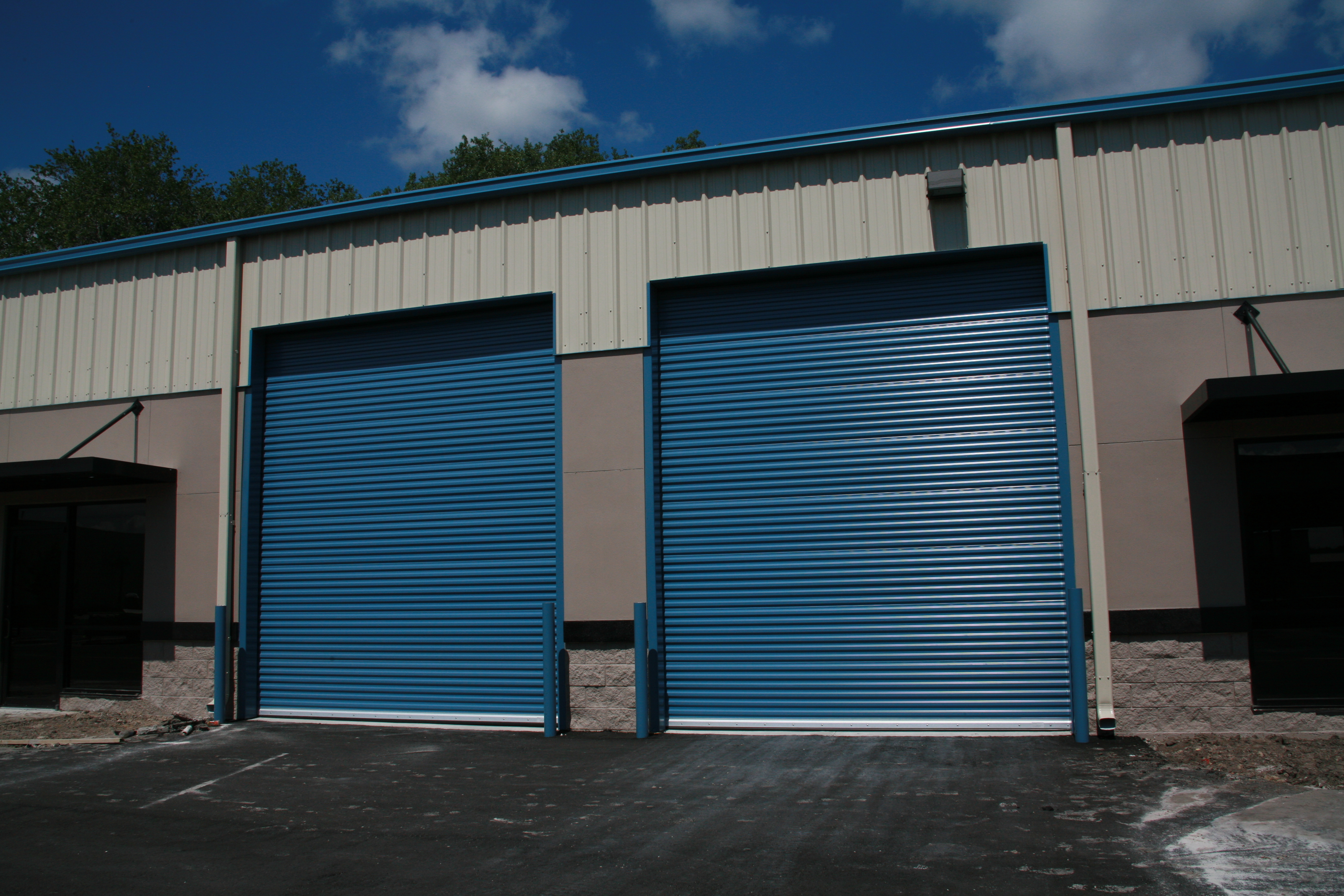 Two Blue Commercial Roll-up Doors Installed on Building