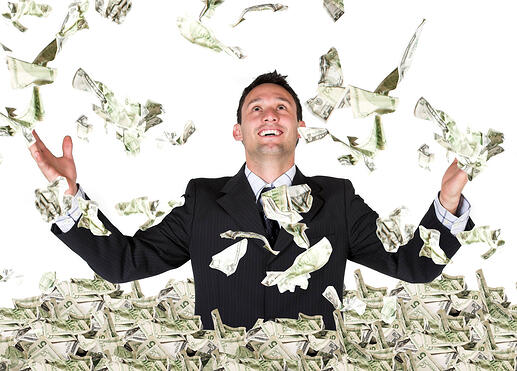 Man playing in the pile of cash he has saved