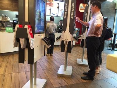 man using a kiosk at mcdonalds