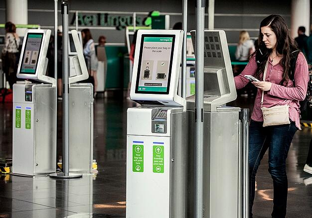 woman standing at a digital kiosk with other kiosks surrounding